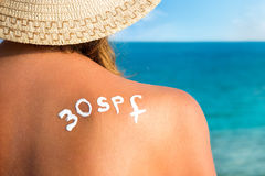 Woman with  sun tan cream on her back over sea background Stock Photography