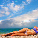 A woman sunbathes on a beach Royalty Free Stock Images