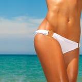 A woman sunbathes on a beach Stock Photos