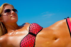 A woman sunbathes on a beach Stock Photos