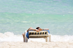Woman sunbathing. In a plastic chair on a beautiful beach in Cuba Royalty Free Stock Image