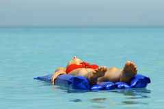 Woman sunbathing on an air mattress Royalty Free Stock Photo