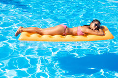 Woman sunbathing on air mattress in the swimming pool Royalty Free Stock Photos