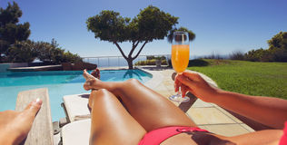Woman sunbathing along a pool with orange juice Stock Photo