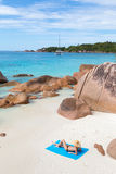 Woman sunbathing at Anse Lazio picture perfect beach on Praslin Island, Seychelles. Woman wearing black bikini and beach hat, sunbathing at Anse Lazio beach on royalty free stock image