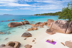 Woman sunbathing at Anse Lazio picture perfect beach on Praslin Island, Seychelles. Woman wearing black bikini and beach hat, sunbathing at Anse Lazio beach on royalty free stock photography