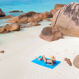 Woman sunbathing at Anse Lazio picture perfect beach on Praslin Island, Seychelles. Woman wearing black bikini and beach hat, sunbathing at Anse Lazio beach on stock photos