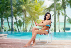 Woman sunbathing and applying sunscreen on beach royalty free stock photos