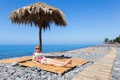 Woman sunbathing as tourist on stony portuguese beach Royalty Free Stock Image
