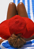 Woman Sunbathing. Attractive Woman Wearing A Red Summer Hat sunbathing on the Beach Royalty Free Stock Photos
