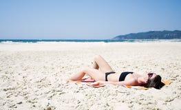 Woman Sunbathing on the Beach Royalty Free Stock Photos