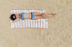 Woman sunbathing on a beach Royalty Free Stock Image