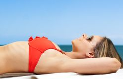Woman sunbathing at the beach Stock Image