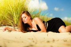 Woman sunbathing on beach. Stock Photo