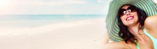 Woman sunbathing on the beach. Woman in sunhat and glasses sunbathing on the beach Royalty Free Stock Photos