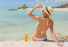 Woman sunbathing on the beach with sunscreen bottle next to her Royalty Free Stock Photography