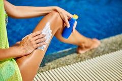 Woman sunbathing in bikini and applying sunscreen stock images