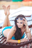 Woman sunbathing in bikini at tropical travel resort. Beautiful young woman lying on sun lounger near pool. Royalty Free Stock Photos