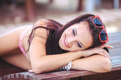 Woman sunbathing in bikini at tropical travel resort. Beautiful young woman lying on sun lounger near pool. Royalty Free Stock Photo