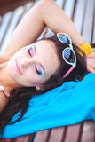 Woman sunbathing in bikini at tropical travel resort. Beautiful young woman lying on sun lounger near pool. Stock Photos