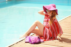 Woman sunbathing in bikini at tropical travel resort. Beautiful young woman lying on sun lounger near pool. Stock Image