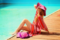 Woman sunbathing in bikini at tropical travel resort. Beautiful young woman lying on sun lounger near pool. Stock Photography