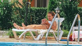 Woman sunbathing in chair by the pool. And using mobile phone stock footage
