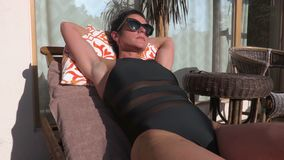 Woman sunbathing on the chair stock footage