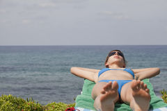 Woman sunbathing on chaise Royalty Free Stock Image