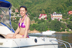 Woman sunbathing on cutter on river Stock Image