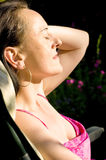 Woman sunbathing on deck chair Stock Photography
