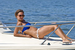 Woman sunbathing on the deck of the yacht Stock Photos