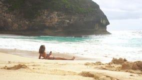 Woman sunbathing, enjoying vacation on ocean, Kelingking beach. Nusa Penida. Indonesia stock video footage