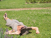 Woman sunbathing. Fine woman lying on the green grass in hot summer Royalty Free Stock Images