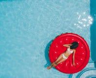 Woman sunbathing on floating mattress in swimming pool. Top view of woman in bikini relaxing on floating mattress in the pool water in hot sunny day. Female stock photo