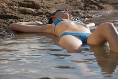Woman Sunbathing In Water Stock Image
