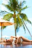 Woman sunbathing on an infinity pool Royalty Free Stock Image