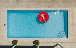 Woman sunbathing on inflatable mattress in pool. Aerial view of female in bikini lying on a floating mattress in swimming pool with her face covered with hat stock photos