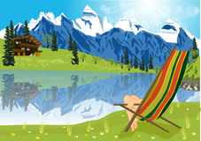 Woman sunbathing on lounge chair beside a lake located at the foot of a mountain Stock Photos