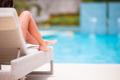 Woman sunbathing on a lounger at tropical resort near pool Stock Image