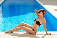 Woman sunbathing near the sunlit pool Stock Photography