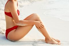 Woman Sunbathing On Tropical Beach. Legs.Sexy Suntan Bikin Woman Legs Relaxing Royalty Free Stock Photos