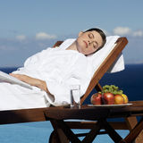 A woman sunbathing by a pool Stock Image
