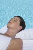 A woman sunbathing by a pool Stock Photo