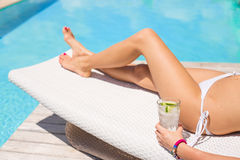 Woman sunbathing by the pool with glass of refreshing cold drink Royalty Free Stock Images