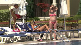 Woman sunbathing by the pool in the resort of Golden Sands, Bulgaria stock video