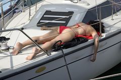 Woman sunbathing in red swimming suit on boat deck in Portoferraio, Province of Livorno, on the island of Elba in the Tuscan Archi Royalty Free Stock Image