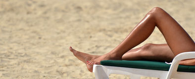Woman sunbathing and relaxing on tanning bed Stock Photo