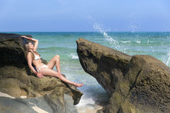 Woman sunbathing on the rocks. Royalty Free Stock Photography