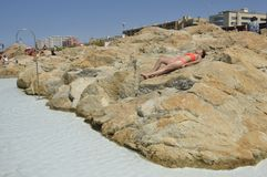 Woman sunbathing on rocks Royalty Free Stock Photography